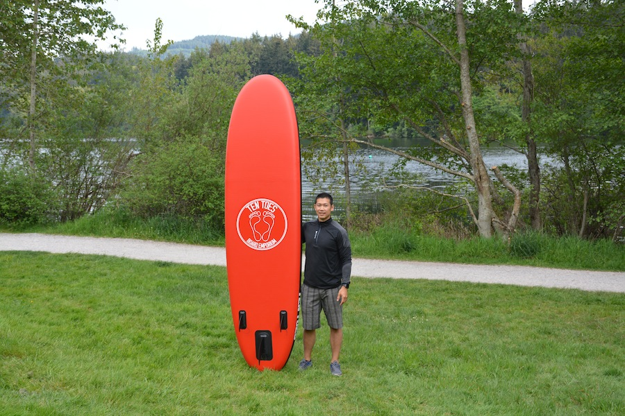 standing beside 10' Weekender stand up paddleboard