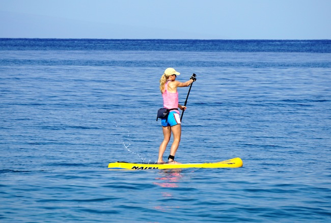 stand-up paddling wearing the Chums Downriver Rolltop bag